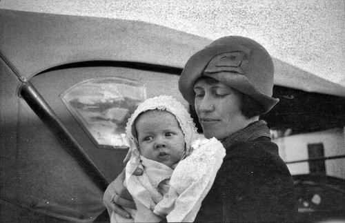 Woman holding baby in front of car
