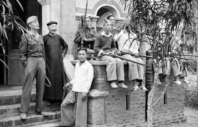 North Vietnam 1950 - Guerilla soldiers sitting on wall of Catholic church in Vĩnh Yên
