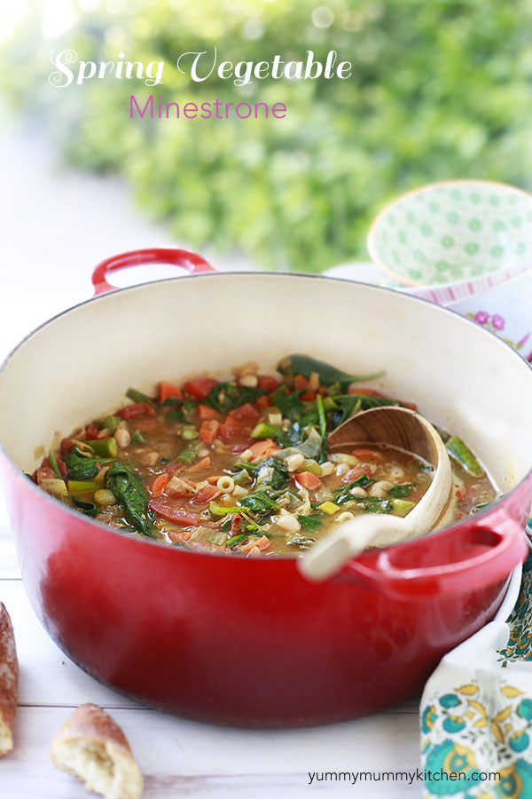 A red pot of spring vegetable minestrone soup with a wooden ladle. Spring minestrone is filled with baby spinach, carrots, asparagus, and other veggies and makes a great vegetarian one pot dinner.
