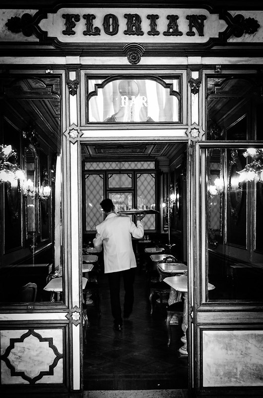 A well dressed waiter makes his way through Venice's Cafe Florian.