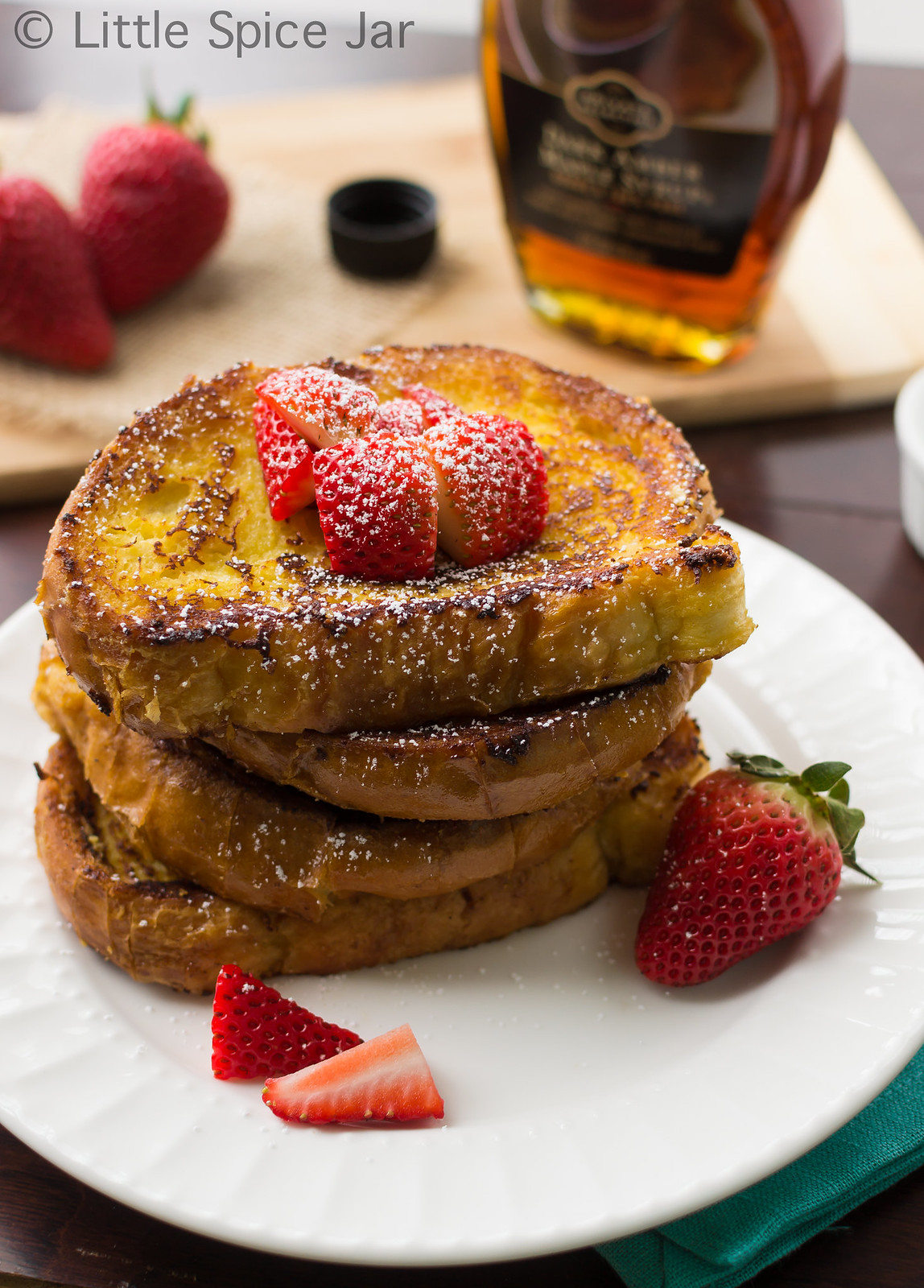stack of creme brûlée French toast on white plate with strawberries and dusted with powdered sugar