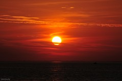 Cloud Slices Sun As Boat Slices Sea - IMRAN™