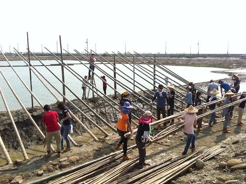 志工分工將竹子搬運上禦寒風坪上搭建。