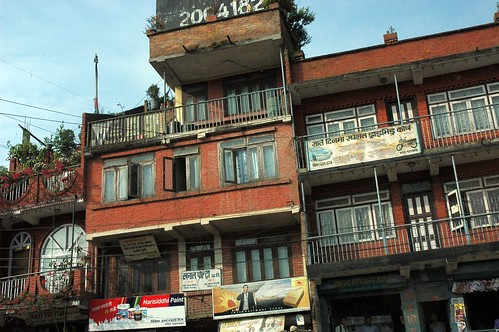 2064182 rugged Nepalese brick apartments, flowers, open windows, stores, magazines on display, banner advertising, Harisiddhi Paint, Kathmandu, Nepal by Wonderlane
