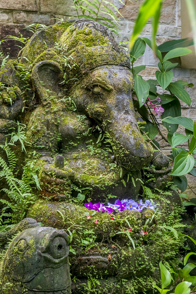 Ganesh the Hindu Elephant Deity covered in moss, ferns and decorated with fresh blooms greets guests as they enter the courtyard