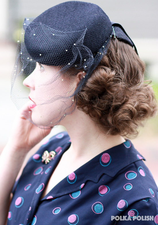 A navy tilt hat with dotted veil tops off this 1940s look