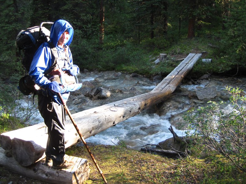 Crossing Wildflower Creek on a log bridge at the BA15 camp on the Baker Creek Trail