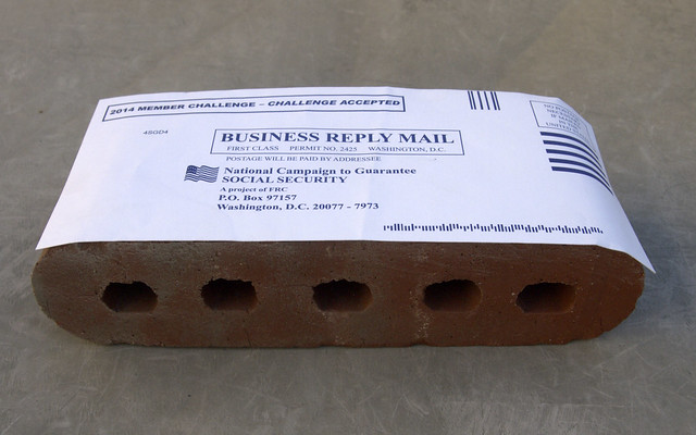 Pre-paid envelope taped to a brick
