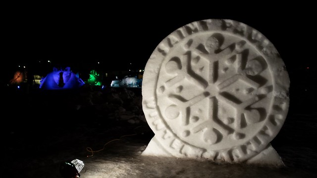 Snow carving of the Winter Carnival logo, with colorful lighted sculptures in the background