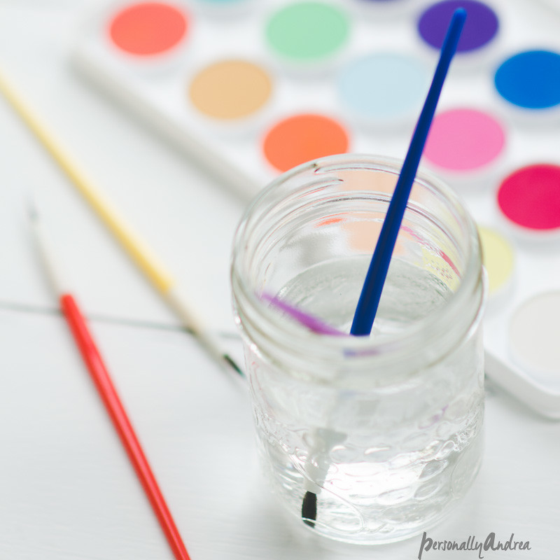 Watercolor paint palette and brushes in mason jar