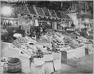Young boy tending freshly stocked fruit and vegetable stand at Center Market, 02/18/1915