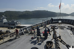 Sailors and Military Sealift Command civilian mariners aboard tUSS Frank Cable (AS 40) heave a line used to moor the ship as it arrives in Sepangar, Malaysia, April 13. (U.S. Navy/MCSN Gabrielle Joyner)