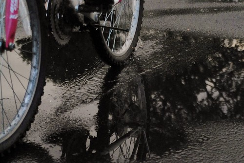 bike wheels reflection in puddle