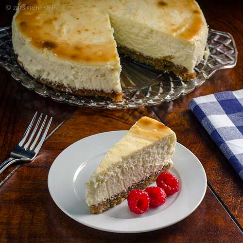 Lemon Cheesecake with Walnut Crust, on plate with whole cheesecake in background