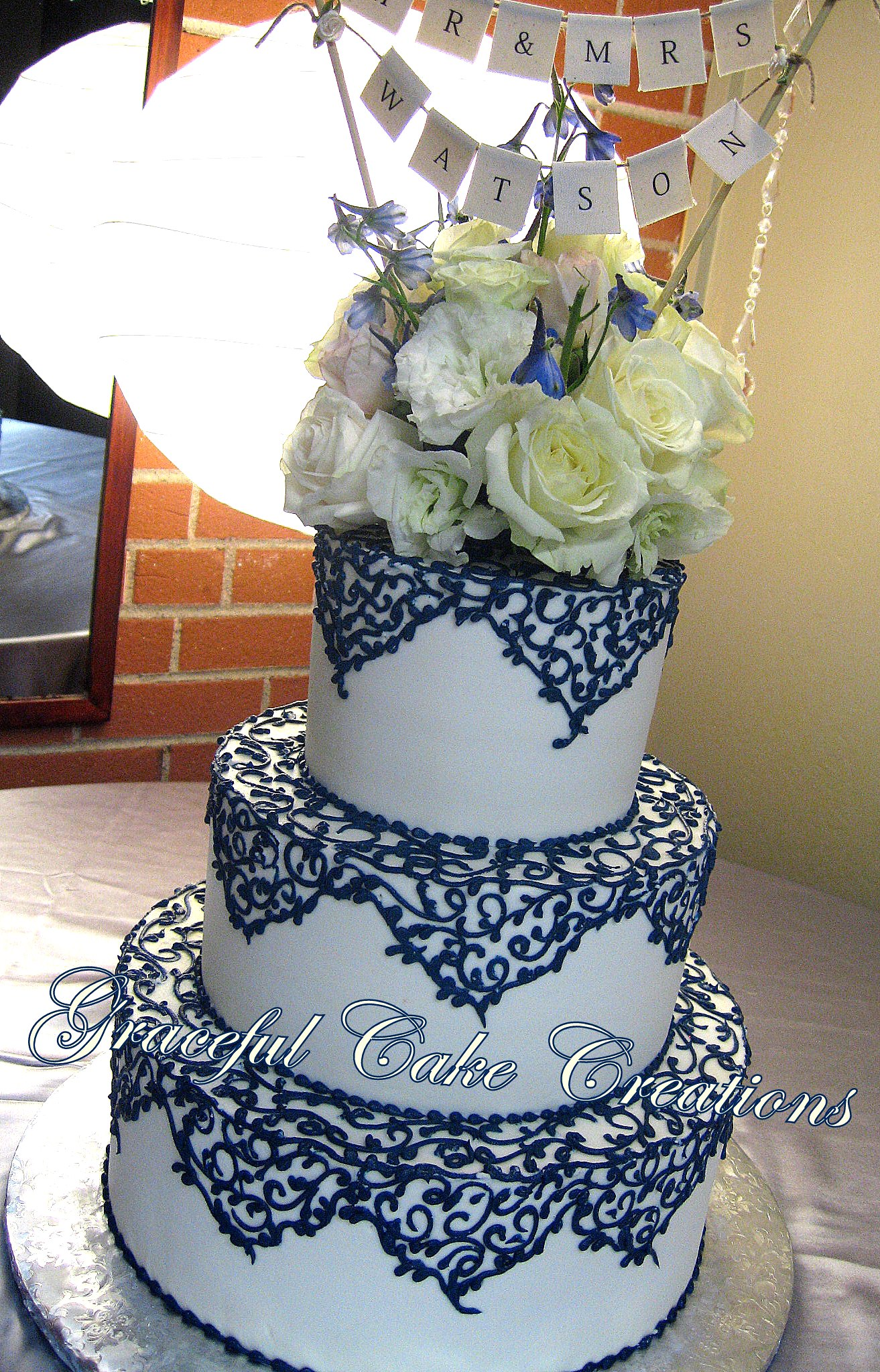 Elegant Ivory Wedding Cake with Navy Blue Lace