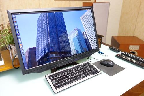 My Room_(2015_02_10)_3 部屋の写真。PC ディスプレイとキーボードとマウスとオーディオ装置用リモコンが置かれたテーブルがあり、奥にはフロント R チャネル用の大きなトール ボーイ型スピーカー システムが1本あり、右端には大きなサブウーファーが置かれている。PC ディスプレイにはUbuntu OSのデスクトップが表示されている。