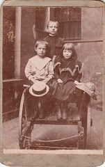 Portrait of three well-dressed children in a handcart (undated)
