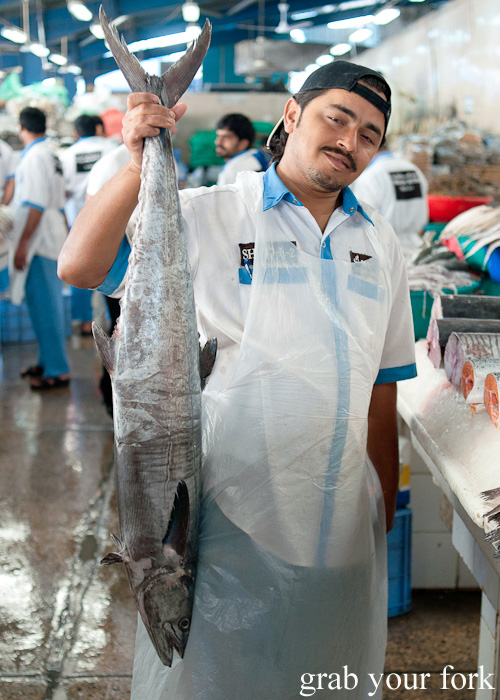 Fishmonger posing with fish at Dubai Fish Market in Deira