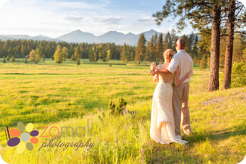 The newly married couple takes a moment to gaze into the sunset and mountains after their beautiful wedding in Seeley Lake Montana