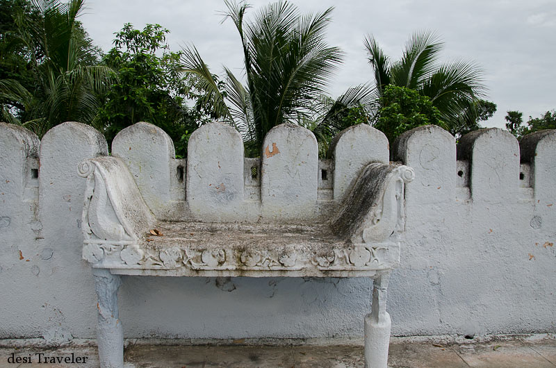 A stone bench on the temple roof with coconut trees in background