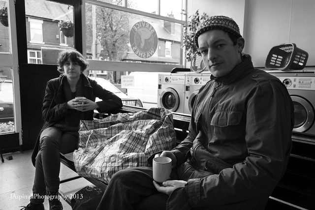 A man and a woman sit with cups of coffee in a laundromat waiting