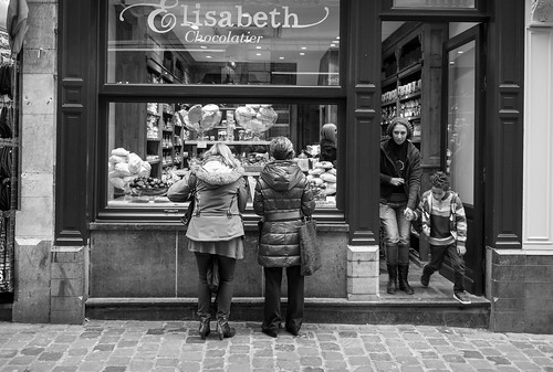 Take time to stop and just wait for things to happen. I was originally photographing the two women window shopping for chocolate in Brussels when a mother and child exited.