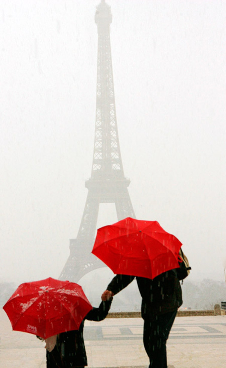 red umbrellas at the eiffel tower in during a hail storm