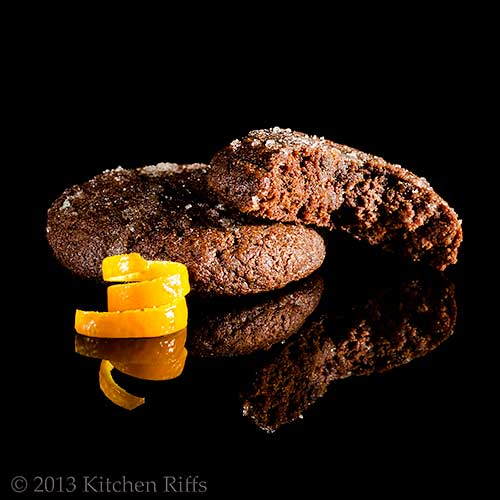 Double Orange Deep Chocolate Cookies with orange peel, on black acrylic