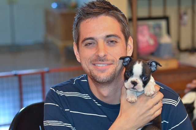A smiling young man looking at the camera holding a Boston Terrier puppy.