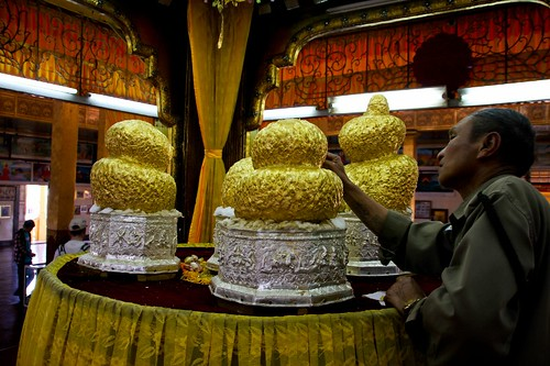 Man putting a gold leaf on a buddha image, Hpaung Daw U Pagoda, Inlay Lake, Myanmar