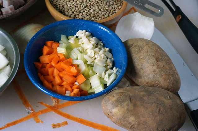 A bright blue bowl sits on a cutting board strewn with carrot and onions scraps. The bowl is filled with pale ivory garlic, pale green celery, and freakishly brightly orange carrots. The brightness is an artifact of photo editing; carrots are just shockingly orange.