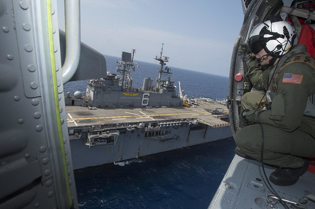EAST CHINA SEA - Naval Aircrewman Philip Franzoni watches out the side hatch of an MH-60S Knighthawk helicopter assigned to Helicopter Sea Combat Squadron (HSC) 25 while while taking off from the flight deck of the forward-deployed amphibious assault ship USS Bonhomme Richard (LHD 6).