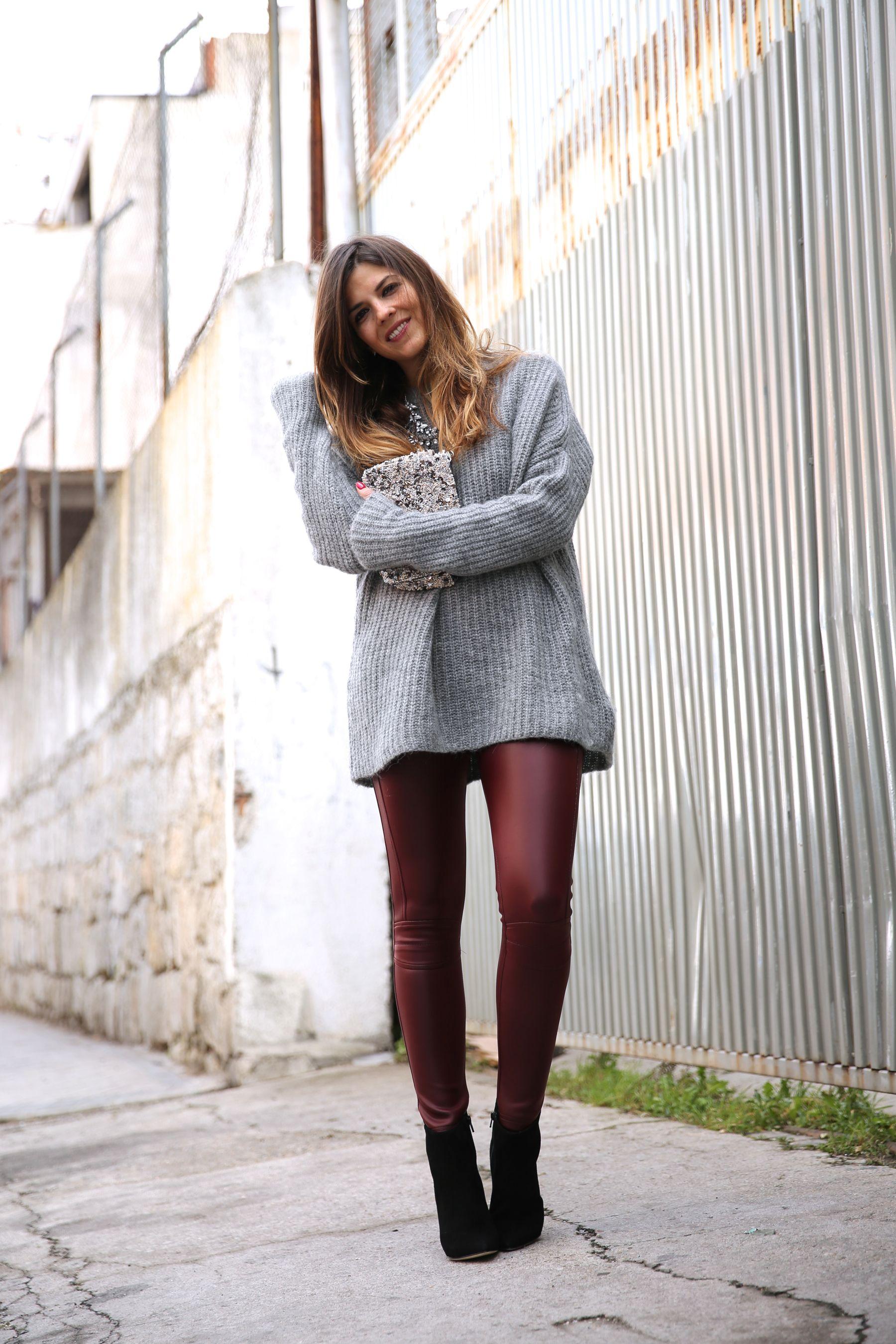 Look casual con leggings de piel burgundy, jersey oversize de punto, clutch de pedrería y botines negros