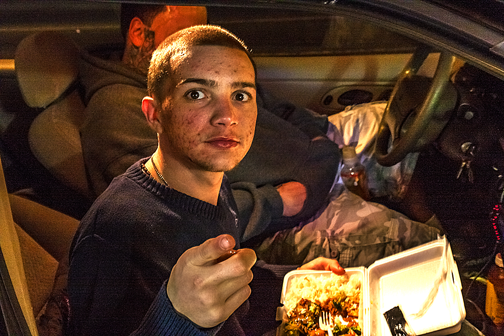 Young-man-eating-Chinese-food-in-car--Frankford