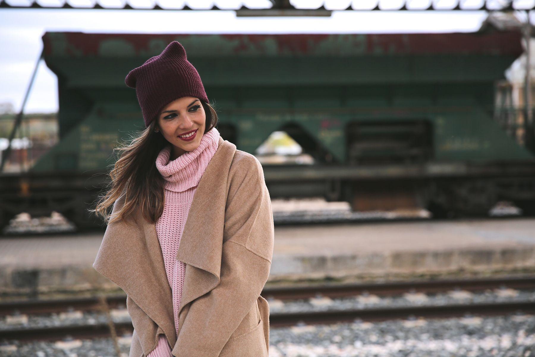 Look casual chic con trench oversize, jersey de punto rosa, vaqueros, botines y gorro de lana burgundy