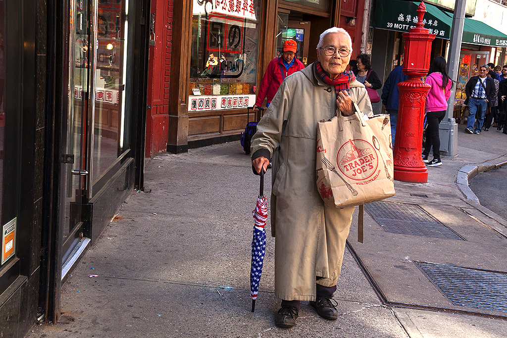 Old woman with red, white and blue umbrella--Chinatown
