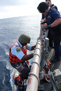 SOUTH PACIFIC- Lt. Joseph Anthony, U.S. Coast Guard Law Enforcement Detachment officer-in-charge, right, watches  Republic of Nauru Police Officer Falzon Laan climb down the accommodation ladder of the Arleigh Burke-class guided missile destroyer USS Kidd (DDG 100) to embark its rigid-hull inflatable boat to conduct a boarding of a fishing  vessel within Nauru's economic exclusive zone in support of the Oceania Maritime Security Initiative (OMSI). OMSI is a Secretary of Defense program that leverages Department of Defense assets transiting the region to increase the U.S. Coast Guard's maritime domain awareness, ultimately supporting its maritime law enforcement operations in Oceania. (U.S. Navy photo by Logistics Specialist 2nd Class Karolina Brooks)