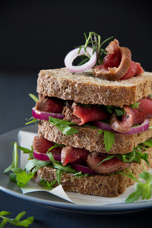 Grain bread sandwich with roast beef, onion and arugula.