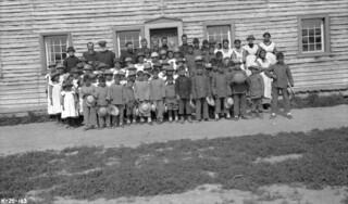 Officials and schoolchildren outside Providence Mission Indian Residential School, Fort Providence, Northwest Territories... / Écoliers et responsables à l'extérieur du Pensionnat indien [catholique] de Fort Providence, Fort Providence (T. N-O)...