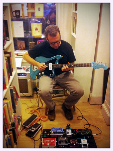 playing guitar at The Spiral Bookcase