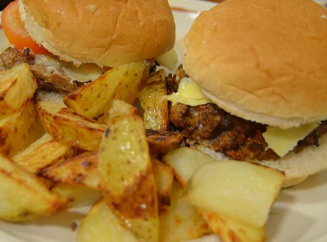 Homemade beefburger in a bun served with potato wedges