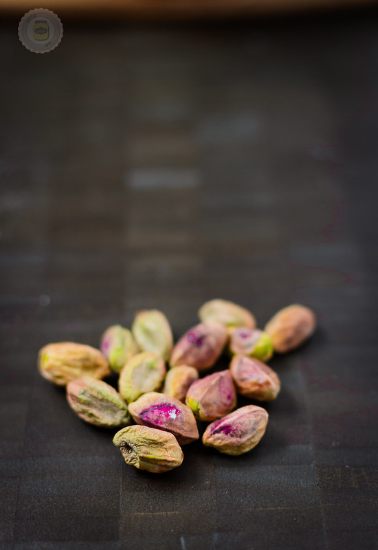 Pistachios pictured on a dark surface
