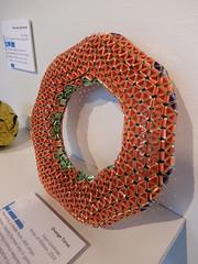 textile(0.0), christmas decoration(0.0), circle(0.0), art(1.0), orange(1.0), wreath(1.0),