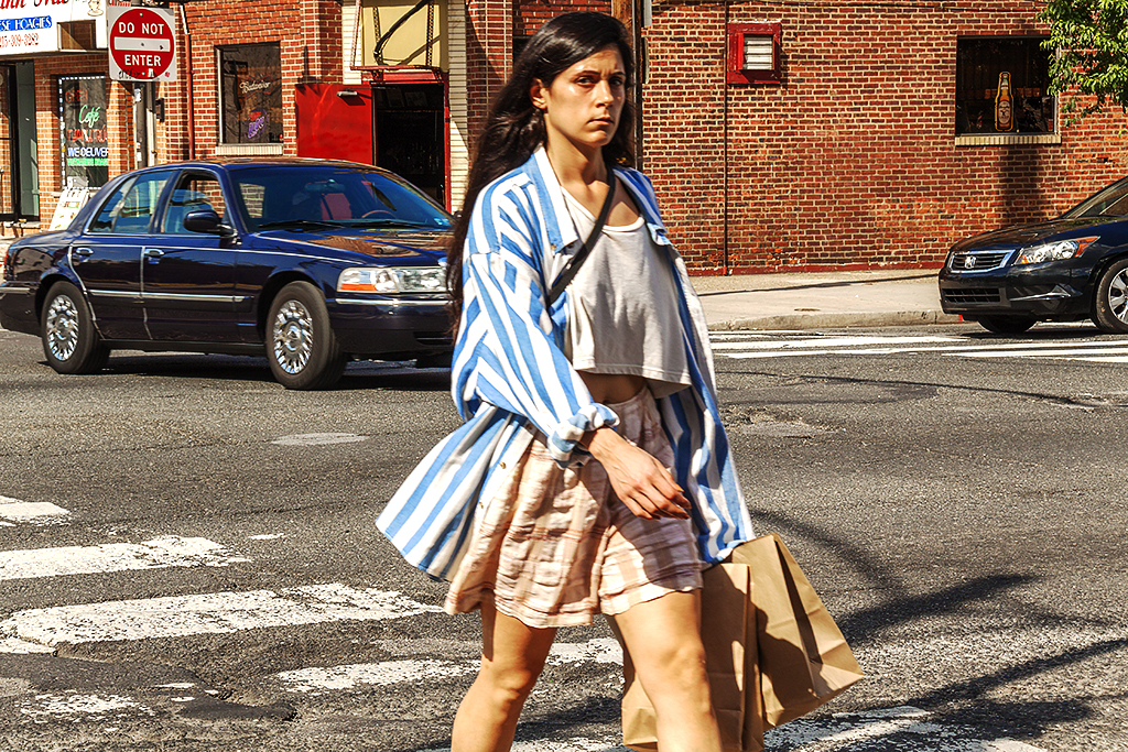 Woman crossing Washington Avenue with Friendly Lounge in background--Italian Market