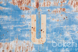 Rusty letter U on a blue gate | Kratie Province, Cambodia