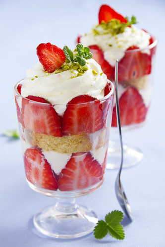 dessert with cookies, strawberries and whipped cream in a glass, selective focus, horizontal