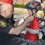 June 8, 2016 - 08:50 - 'Deputy Sheriff Brian Grazidei adjusts a child's bike helmet prior to a Suffolk County Sheriff's Office Bike Rodeo in Bayport, NY.