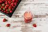 Fresh juice, shake, milkshake of strawberries in a mason jar with a straw. Pile of juicy ripe organic fresh strawberries in a black crate. Strawberry fresh drink. Light rustic wooden background