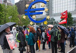 Demonstranten mit Regenschirmen vor großem Euro-Zeichen. Im Hintergrund SDAJ und DKP-Fahnen.