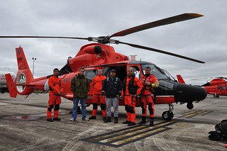 Two survivors from a vessel with stability issues in the Gulf of Mexico take a photo with the Coast Guard Air Station New Orleans aircrew who rescued them and transported them to the air station in Belle Chasse, La., Nov. 26, 2013. The vessel began experiencing stability issues Monday, about 30 miles offshore of Mobile, Ala. (U.S. Coast Guard photo by Air Station New Orleans)